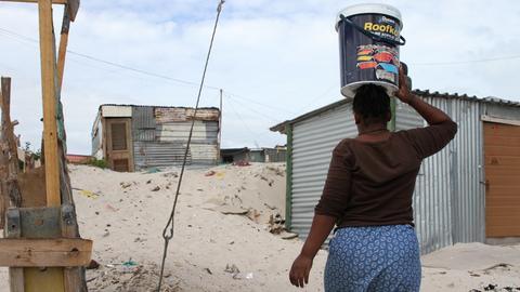 Eine Bewohnerin in einem Armenviertel außerhalb Kapstadts trägt einen Wassereimer auf dem Kopf. Sie muss täglich Wasser von einem kommunalen Wasserhahn nach Hause schleppen.