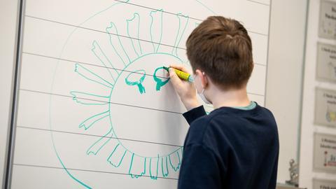 Ein Schüler zeichnet ein Coronavirus an die Tafel.