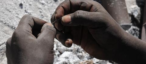 Eine 14-Jährige hält in einem Steinbruch in Burkina Faso einen Metalldraht.