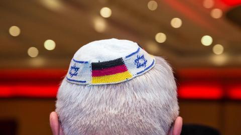 Ein Mann trägt eine Kippa mit israelischer und deutscher Flagge