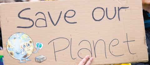 Demonstrationsschild mit der Aufschrift Save our Planet - rettet unseren Planeten