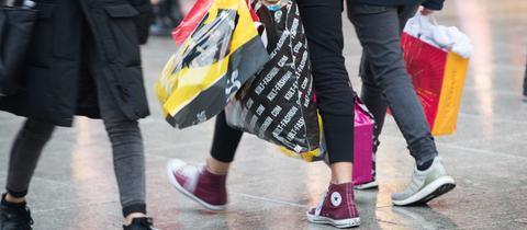 Zwei Menschen spazieren mit vollen Einkaufstüten über die Zeil