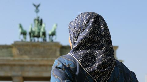 Eine Frau mit Kopftuch vor dem Brandenburger Tor