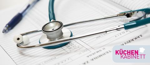 Stetoskop, Kuli und Dokument liegen auf Tisch