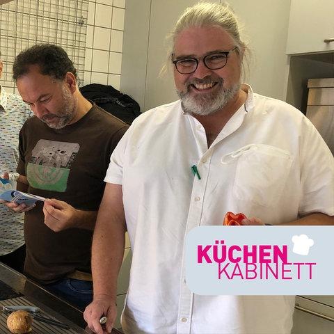 drei Männer stehen in einer Küche und kochen, ein Mann schaut in die Kamera und lacht