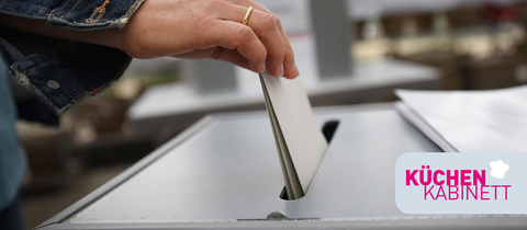 Ein Stimmzettel wird in eine Wahlrune gesteckt