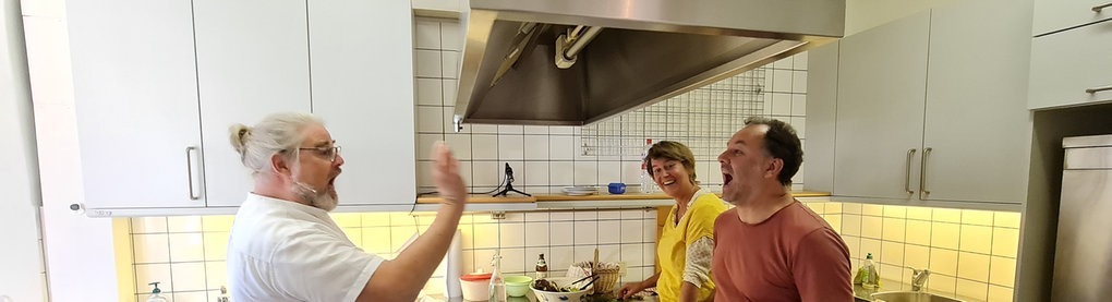 Industrieküche mit Kochinsel in der Mitte, Mann links würft Mann rechts etwas in den Mund, Frau rechts im Hintergrund schaut lachend zu