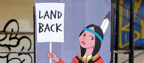 """Gemälde mit einer Ureinwohnerin, die ein Schild mit der Aufschrift """"Land Back"""" trägt"""