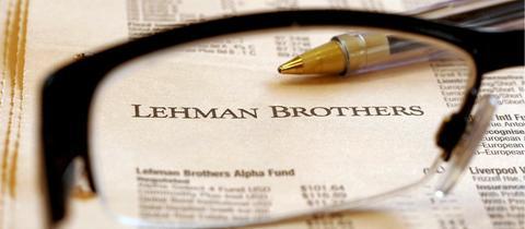 Eine Brille und ein Stift liegen auf einer Zeitung mit den Kurswerten der Lehman Brothers Zertifikate