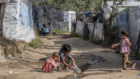 Drei Kinder spielen an einem kleinen Wasserlauf auf einem Weg zwischen Zeltbaracken