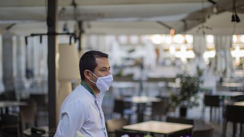 Ein Kellner mit Mund-Nasen-Schutz wartet in der Innenstadt von Madrid auf Kunden.