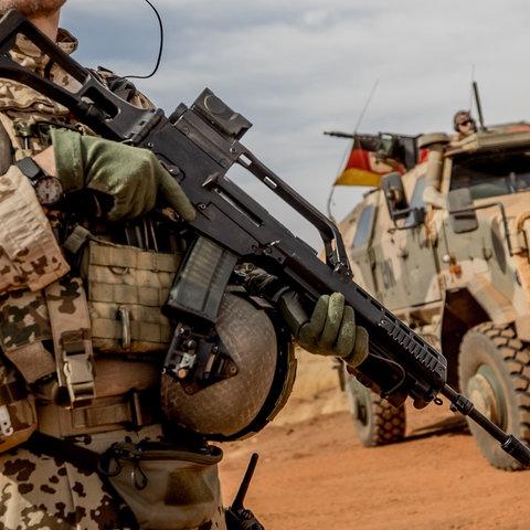 Deutscher Soldat in Wüste vor Truppentransporter