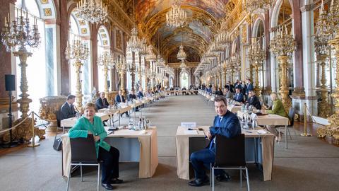 Merkel und Söder sitzen in prunkvoller Halle und schauen in Kamera