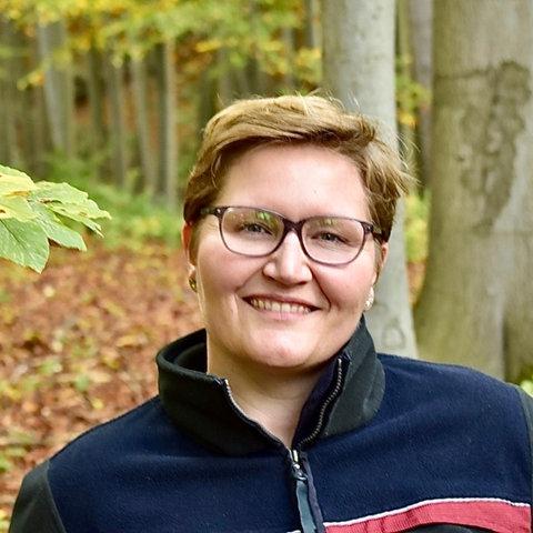 Frau mit Brille und kurzen, blonden Haaren steht im Wald