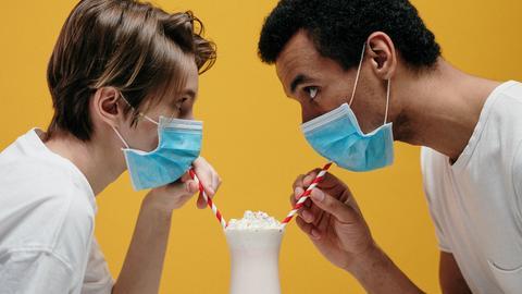 Ein junger Mann und eine junge Frau versuchen Milkshakes zu trinken - trotz Gesichtsmasken