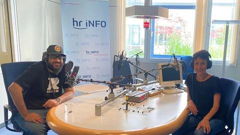 Mann mit roter Mütze sitzt links in einem Tonstudio, Frau mit Kopfhörer sitzt rechts - beide lächeln in die Kamera