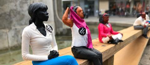 Kleine Figuren von Flüchtlingen sitzen in der Darmstädter Innenstadt.