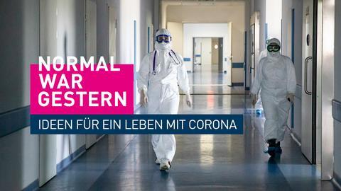 Zwei Personen laufen in Schutzkleidung durch Krankenhausflur