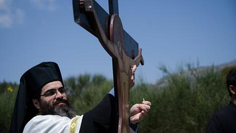 Ein griechisch-orthodoxer Priester vor einem Kreuz.