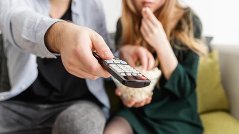 Paar auf der Couch, das um die Fernbedienung streitet