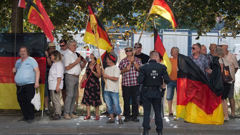 Pegida-Demonstranten stehen in Dresden an einer Straße und schwenken Deutschland-Fahnen
