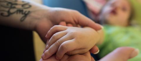 Eine Pflegefachkraft hält die Hand eines pflegebedürftigen Kindes.