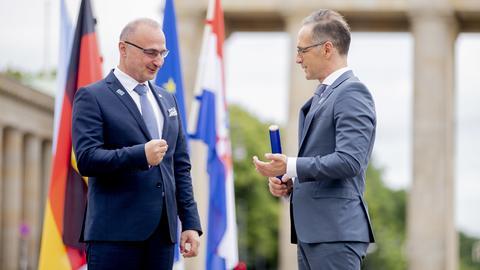 Heiko Maas, Außenminister, und Gordan Grlic Radman, Außenminister der Republik Kroatien, unterhalten sich vor dem Brandenburger Tor.