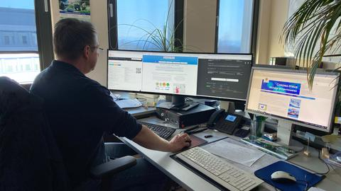Polizist sitzt vor mehreren PC-Bildschirmen