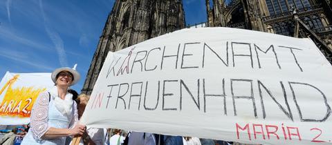 """Plakat bei einer Demo mit der Aufschrift """"Kirchenamt in Frauenhand"""""""