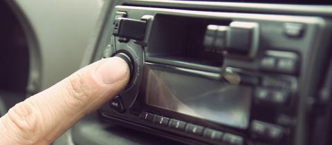 Hand die Autoradio bedient