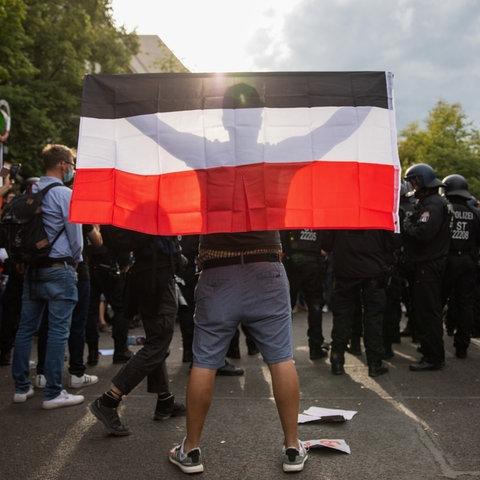 Ein Mann hält eine Reichsflagge bei einem Protest gegen die Corona-Maßnahmen vor der russischen Botschaft.