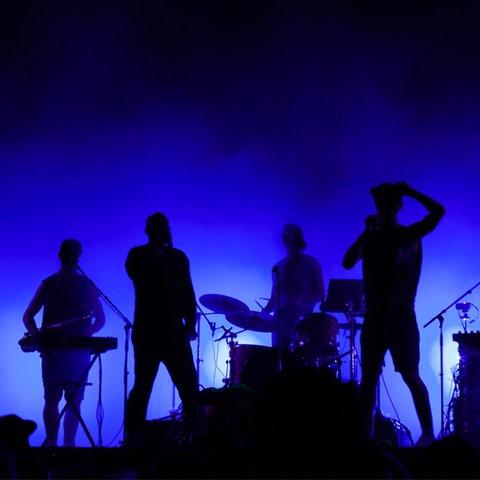 Eine Band steht vor blauem Hintergrund.