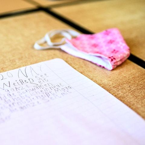 Block mit Kinderschrift liegt auf Holtisch, daneben liegt eine rosa Mund-Nasen-Maske