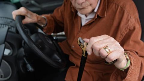Eine Seniorin mit einem Gehstock sitzt hinter dem Steuer eines Autos