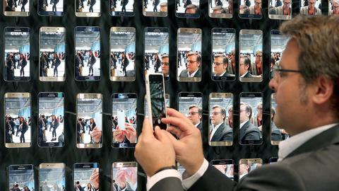 Ein Mann fotografiert eine Wand voller Smartphones bei der Funkausstellung Berlin