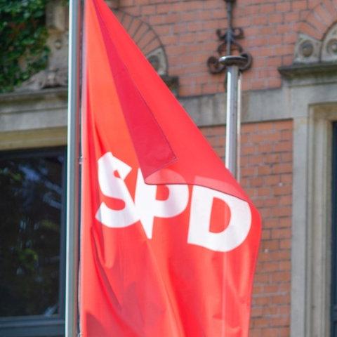Rote SPD-Fahne weht an Fahnenmast vor Gebäude
