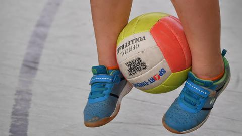 Kind hüpft mit einem Ball zwischen den Füßen