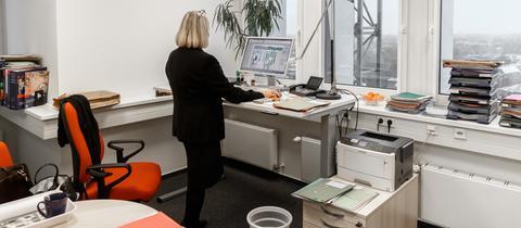 Frau steht an einem erhöhten Schreibtisch im Büro