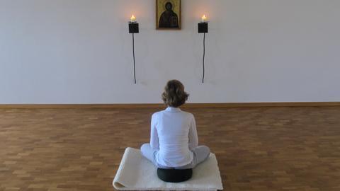 Eine Gläubige meditiert in einem Meditationraum eines Exerzitienhauses.