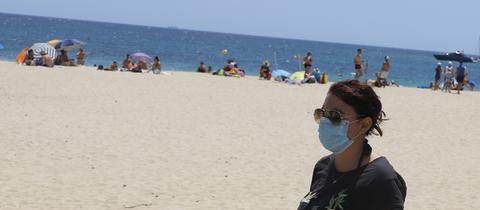 Eine Frau trägt eine Maske am Strand in Spanien