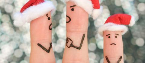 Finger einer Hand mit Weihnachtsmützen, die streiten