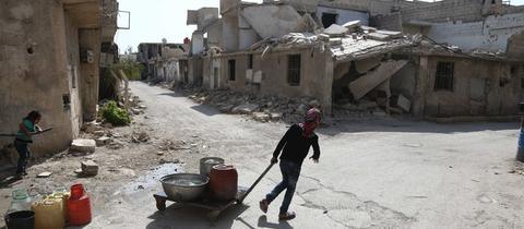 Mädchen zieht vor zerstörten Häuser in Ghouta, Damaskus einen mit Wasserbehältern gefüllten Wagen (21.08.2017)