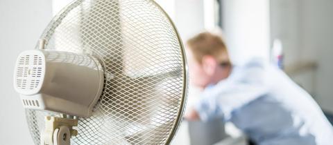 Ein Ventilator steht in einem Büro und ein Mann steht im Hintergrund am Fenster