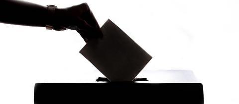 Ein Wahlbrief wird in Wahlurne eingeworfen