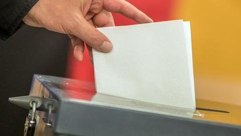 Ein Stimmzettel wird in eine Wahlurne gesteckt