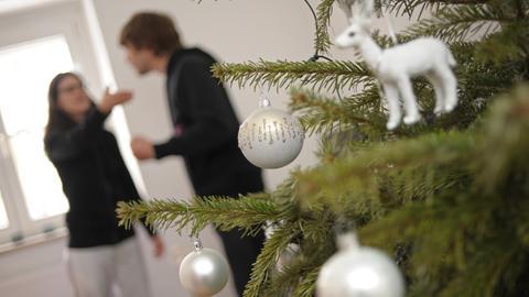 streitendes Paar vor dem Weihnachtsbaum