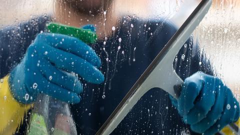 Eine Putzkraft putzt ein Fenster