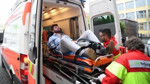 Rettungsassistenten heben in Gießen einen Mann in einen Rettungswagen