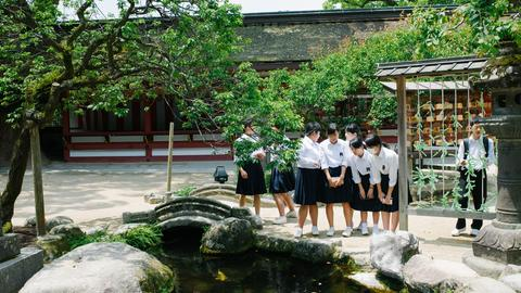 Japanische Schüler*innen in Uniform an einem Teich