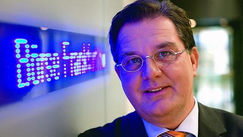 Der Journalist Stefan Wolff steht vor einem Schild mit der Aufschrift Börse Frankfurt